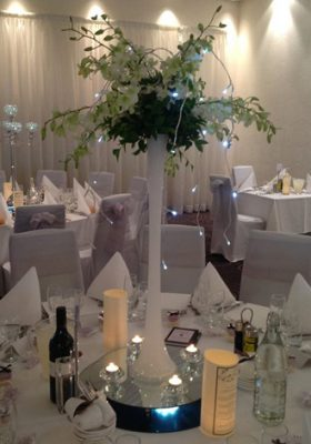 tall white vase with orchids centrepiece